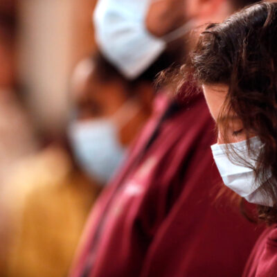 Basilica of Our Lady of Geneva. Christians wearing surgical mask at mass.